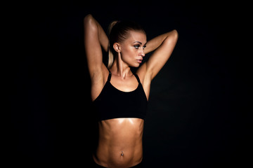 Fit girl doing triceps exercises with dumbell. Black background.