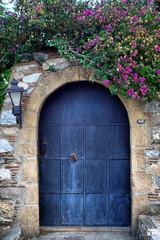old retro wooden blue door and pink bougainvillea
