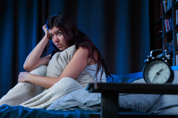 Photo of unhappy woman with insomnia sitting on bed next to alarm clock