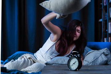 Portrait of dissatisfied woman with insomnia throws pillow sitting on bed next to alarm clock