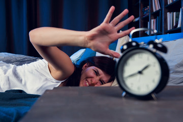 Photo of dissatisfied woman with insomnia stretching arm to alarm clock at night