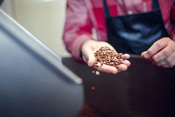 Photo of young businessman holding roasted coffee beans near industrial coffee grinder