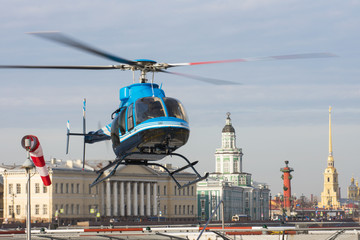 Small helicopter takes off from the helipad in St. Petersburg, against the backdrop of the Kunstkamera, the arrow of the Vasilyevsky Island and the Peter and Paul Fortress.