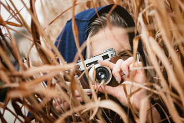 Young attractive girl in hoodie and black glasses takes a photo on retro photo camera in leather case, is standing in the thicket of reeds. Close-up portrait