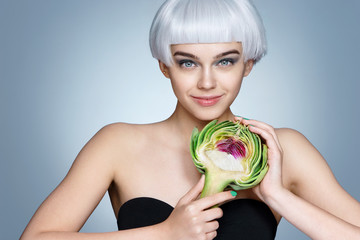 Smiling woman with half of artichoke. Photo of pretty blonde woman on blue background. Detox concept