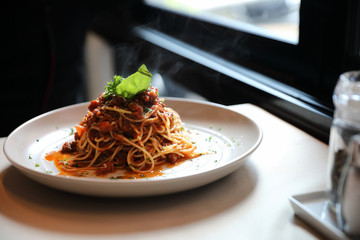 spaghetti Bolognese with minced beef and tomato sauce garnished with parmesan cheese and basil , Italian food