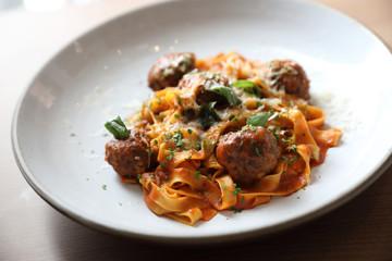 Spaghetti pasta with beef meatballs and tomato sauce on wood background . italian food