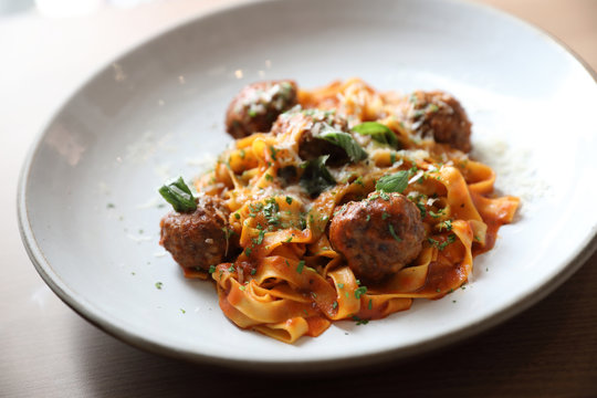 Spaghetti pasta with beef meatballs and tomato sauce on wood background . italian food