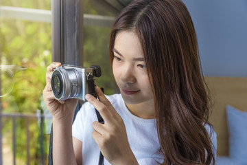 Young attractive asian woman using her camera to take picture of her garden through her bedroom window