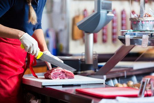 Woman in butcher shop selling meat fillet on a board