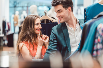 Woman and man discussing color of dress on clothing line in fashion store