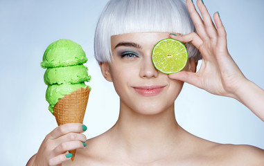 Funny young girl holding waffle cone with ice cream and green lime. Photo of smiling blonde girl on blue background. Happy lifestyle