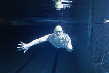 Man in swimming pool. Underwater