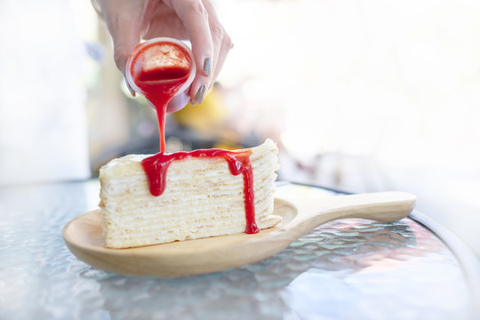 Red strawberry jam is pouring on a beautiful cake.