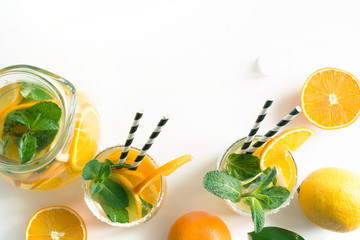 Fresh summer lemonade with citrus, orange and mint on yellow background. Top view and copy space.