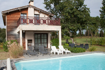 luxury villa home in summer holiday resort with swimming pool and sun chairs