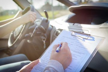 Examiner filling in driver's license road test form