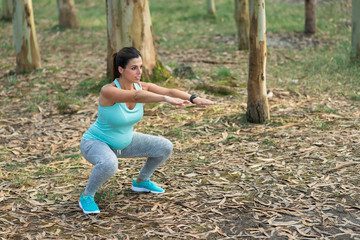 Fitness pregnant woman doing squats for strengthen pelvic floor muscles and legs. Healthy pregnancy exercise.