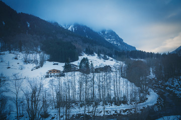 Dark gloomy winter landscape with snow in a mountain valley with village, forested peaks and grey clouds in the Austrian alps