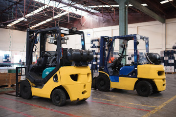 The forklift is in a large and light warehouse. Yellow color.
