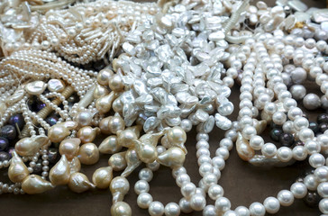 Heap of various pearl necklaces as background