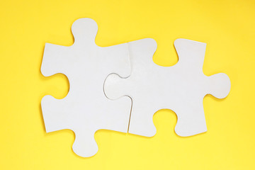 Group of white paper jigsaw puzzles on yellow background