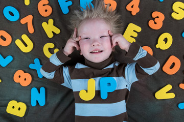 Happy charming Caucasian blond's kid in colored clothes playing with plastic letters. Learning the alphabet, preparing for school. Education for kindergarten and preschool children. Black background