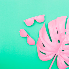 pink sunglasses and tropical palm leaves of monstera on green background. fashion creative concept. minimal and surrealism