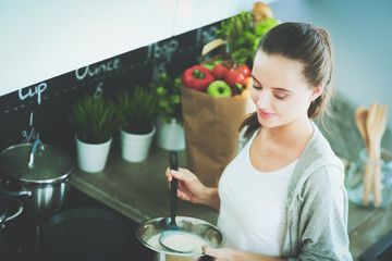 Young woman prepares pancakes in the kitchen while standing near the table. Woman in the kitchen. Cooking at kitchen.