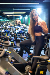 Attractive young girl with towel taking a break after cycling training in gym