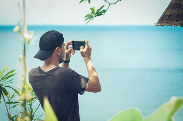 Young man in a cap taking photo of seascape with his cellphone