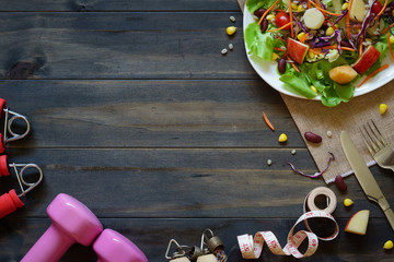 Fresh healthy salad with dumbbells, jump rope, tape measure and excercise equipment on wood background top viwe with copy space. For dieting, fitness and active healthy lifestyles Concept.