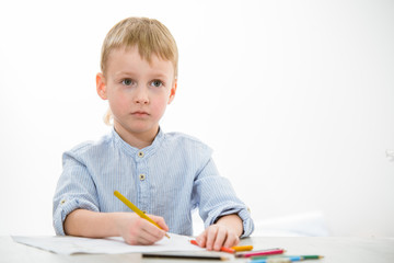 Serious boy 6 years old with a pencil sitting at the table in class