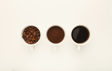 Roasted whole and ground coffee beans in cups, top view, white i