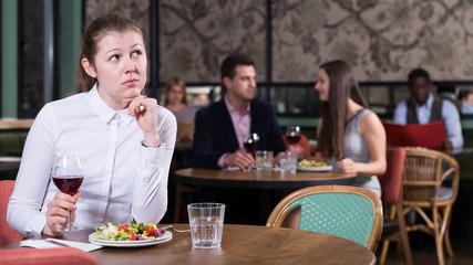 Upset girl dining alone in restaurant