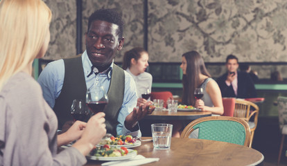 Confident African American businessman with female partner having dinner and drinking red wine at restaurant
