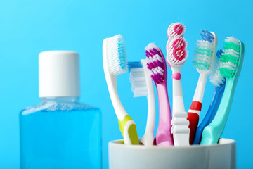 Toothbrushes in cup with mouthwash bottle on blue background