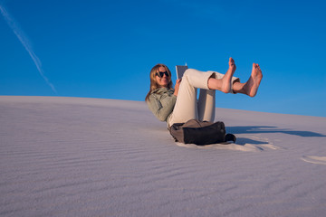 Young woman, blonde in the desert uses tablet and has fun