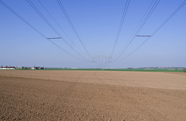Power Lines: Overhead high-voltage power line over a plowed field in Eastern Thuringia in springtime