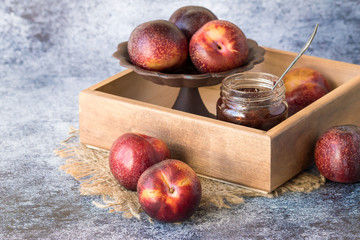 Fresh large plums and a small glass round jar with sweet jam in a wooden box on a blue background.