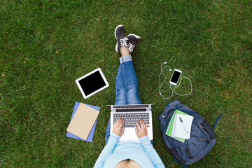 Girl with laptop sitting on the green grass