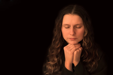 a woman praying with folded hands. girl with closed eyes on black background. concept memory, sorrow, loss, prayer, religion, humility, experience, problem. Woman in deep thought.