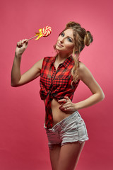 Cheerful young woman with lollipop.