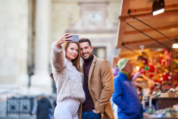 A beautiful young couple taking a selfie with christmas market in the background.