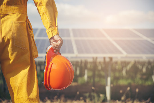 Electrical worker or engineer holding safety hat stand at power plant.Foreman wearing orange safety suit and looking at solar panel background.Safety Engineer concept.