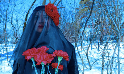 Portrait of a woman in a black burqa with red flowers in the cemetery in winter. A Muslim in nature.