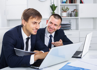 two young males coworkers working in firm office
