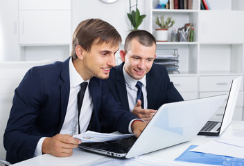 cheerful two men coworkers working on computers in firm office