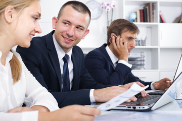 Positive coworkers working and talking on phone