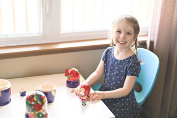 Child girl play on the livingroom with Nesting Dolls Matryoshka